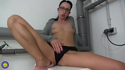 Brunette mature masturbates in glasses