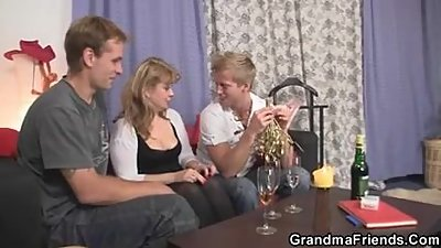 Granny enjoys two cocks in mouth and..