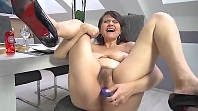 Mature shoving a dildo in her hairy..
